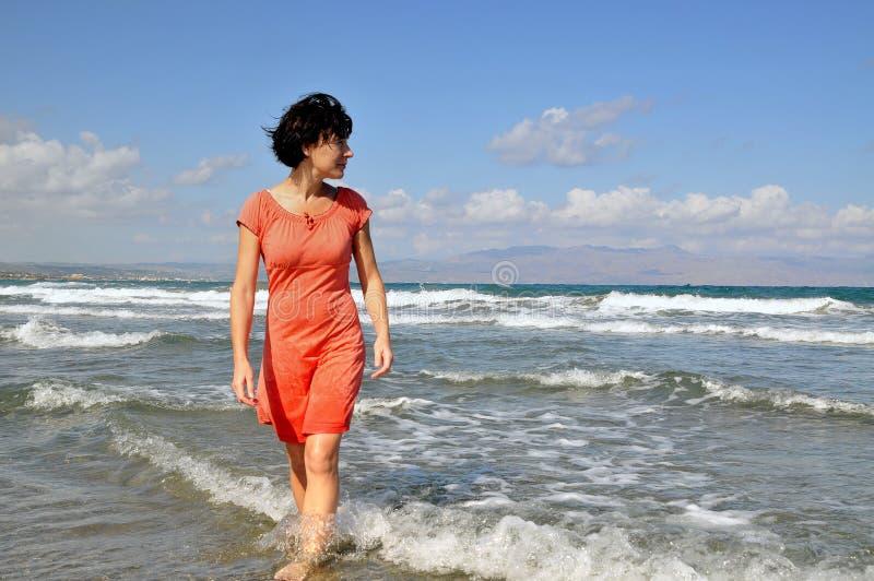 Femme marchant dans l'eau regardant de côté images libres de droits