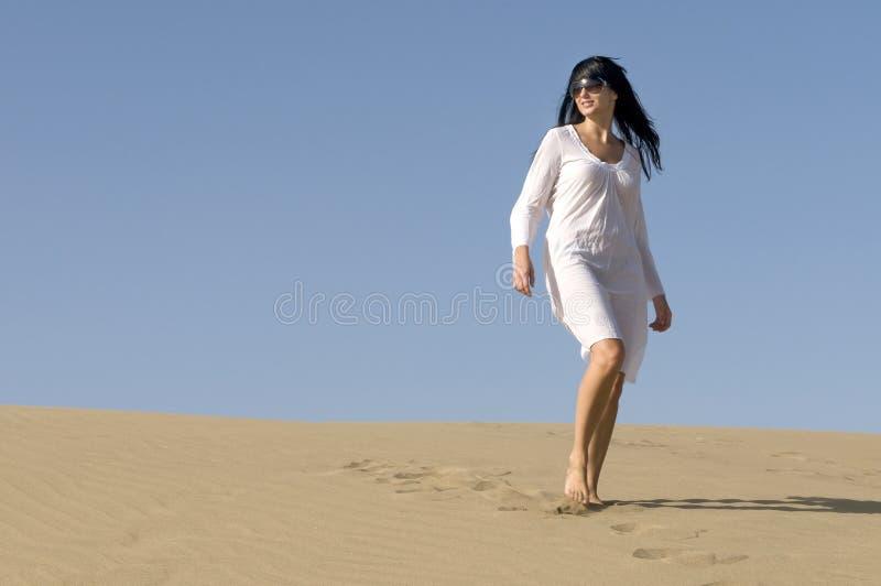 Femme marchant dans les vêtements blancs s'usants de désert photos stock