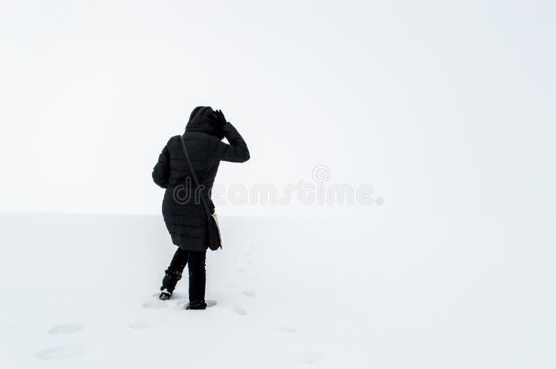 Femme marchant dans un domaine neigeux image stock