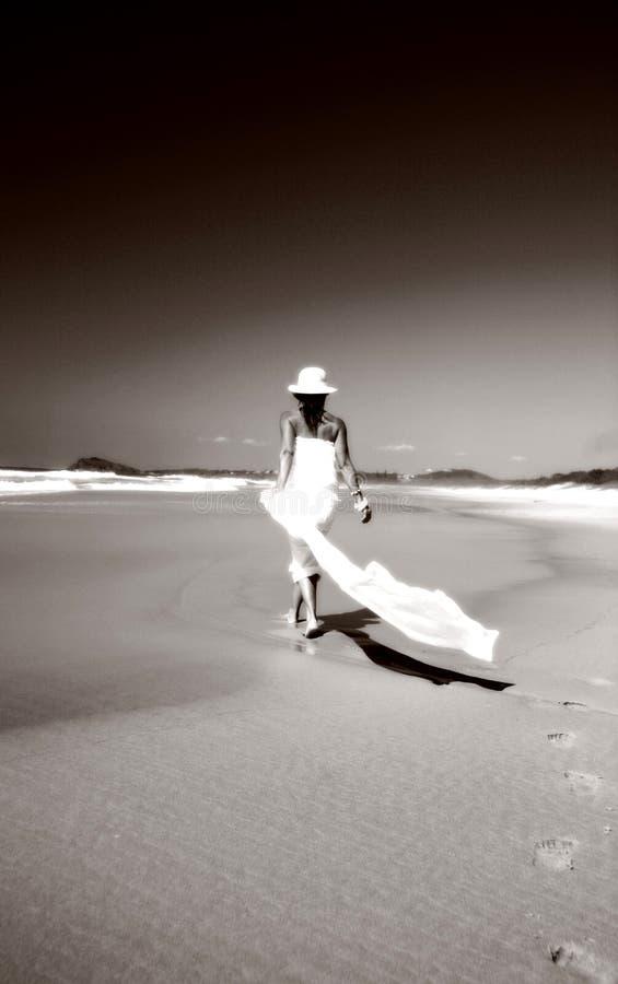 Femme marchant le long de la plage images stock