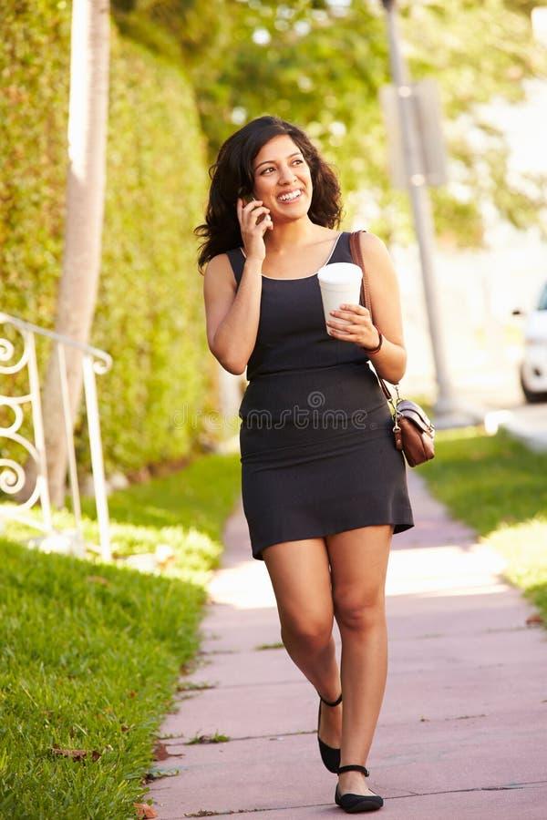 Femme marchant le long de la rue pour travailler utilisant le téléphone portable image stock