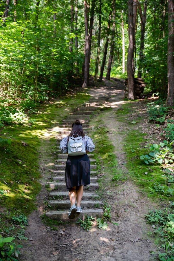 femme marchant par de vieux escaliers dans la forêt image stock