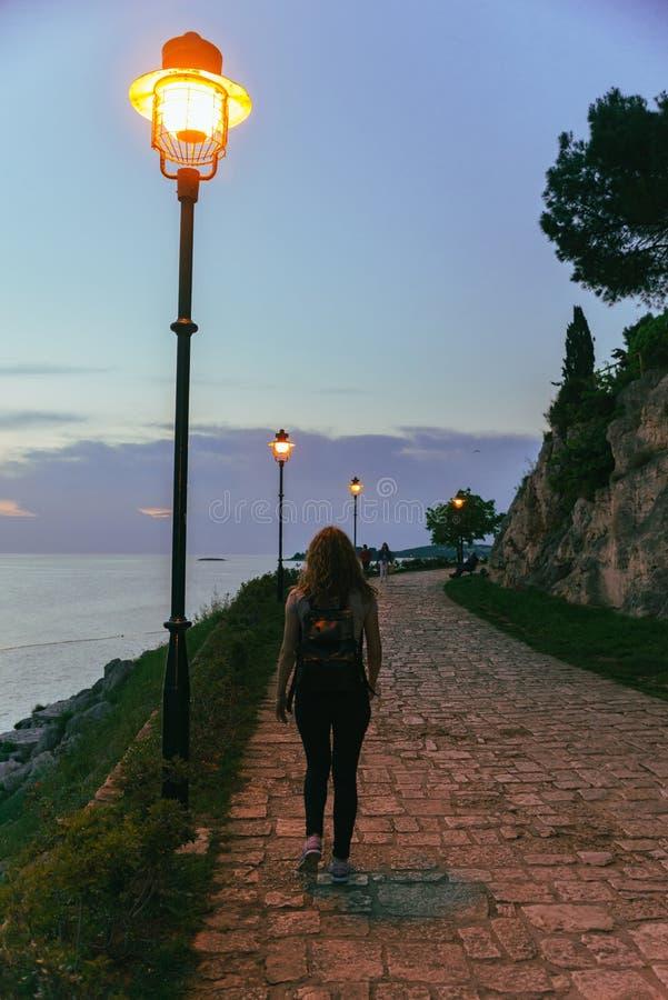 femme marchant par le parc près de la mer sur le coucher du soleil image stock