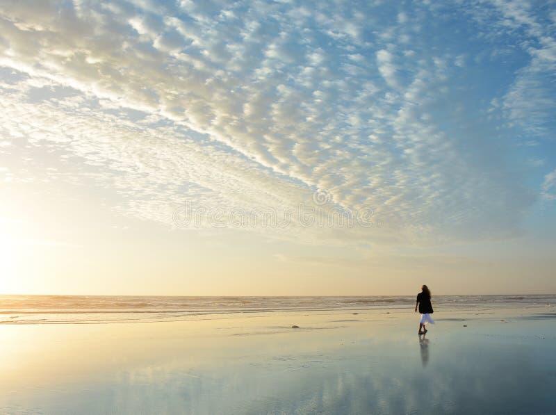 Femme marchant sur la plage au lever de soleil photos libres de droits