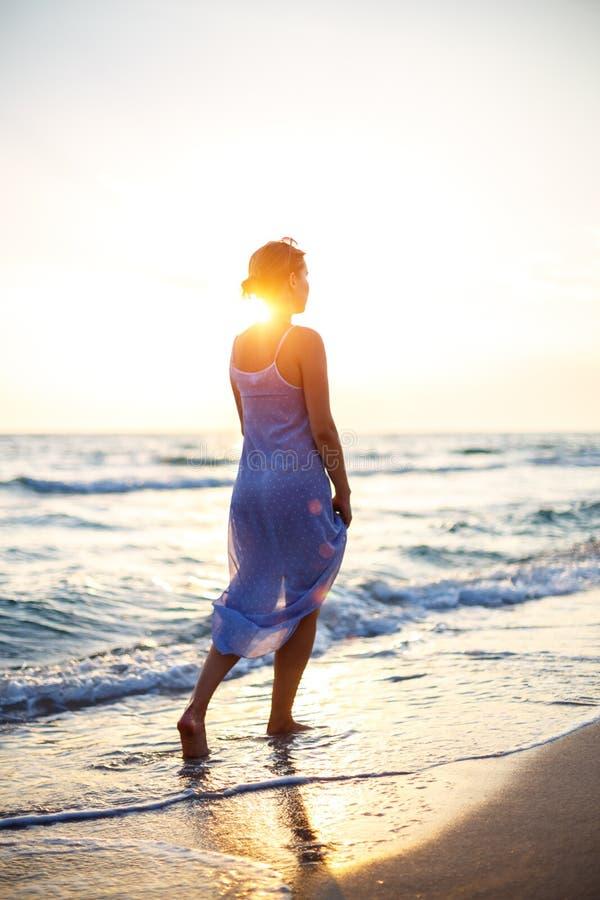 Femme marchant sur la plage dans le ressac au coucher du soleil images libres de droits