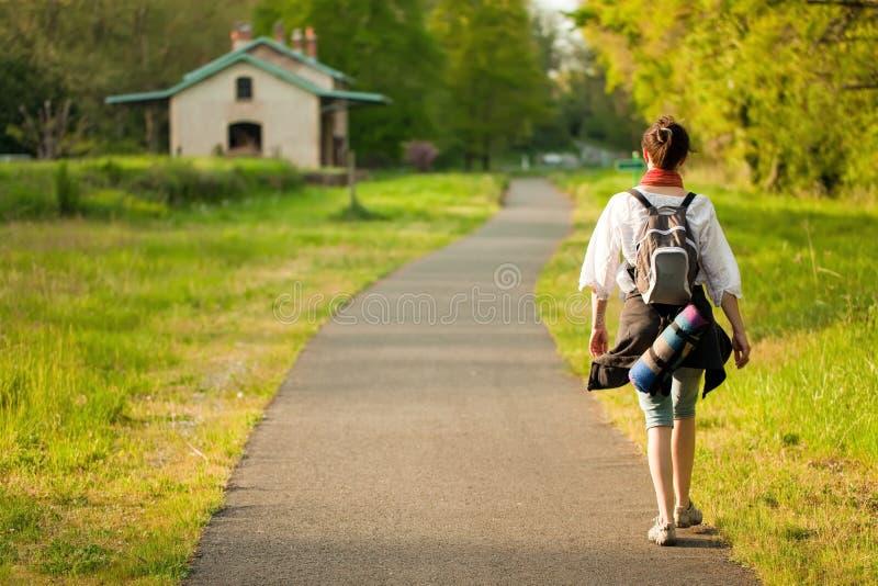 Femme marchant sur la route de campagne images libres de droits