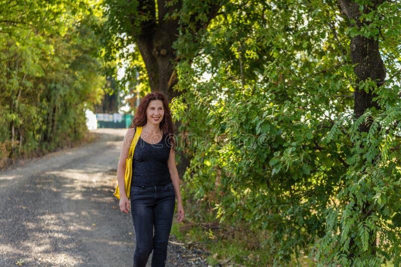 Femme marchant sur le chemin de terre dans la campagne photo stock