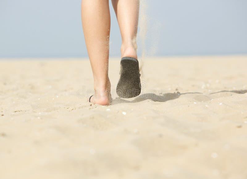 Femme marchant sur le sable à la plage dans des pantoufles photo stock
