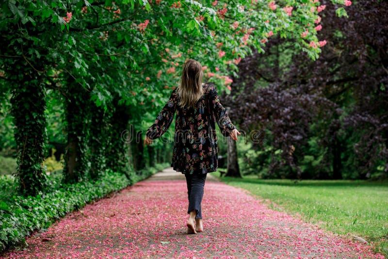 Femme marchant vers le bas nu-pieds ? l'all?e avec des arbres de fleur photos stock