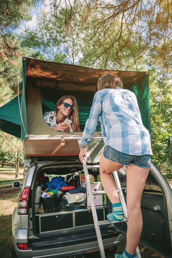 Femme marchant vers le haut de l'échelle à la tente au-dessus de la voiture photographie stock
