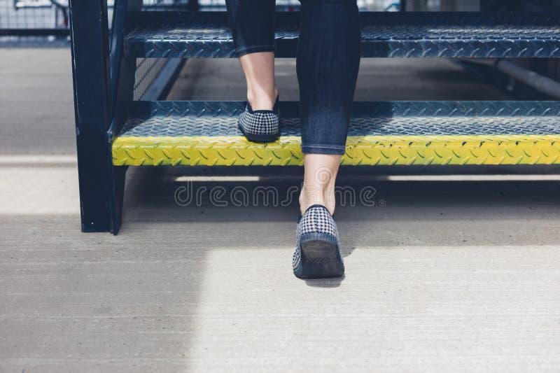 Femme marchant vers le haut des escaliers en métal image libre de droits