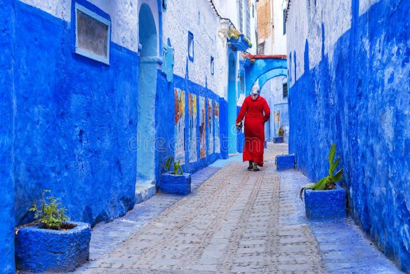 Femme marocaine dans le jellaba traditionnel rouge de vêtements marchant sur une rue en Médina de Chefchaouen images libres de droits