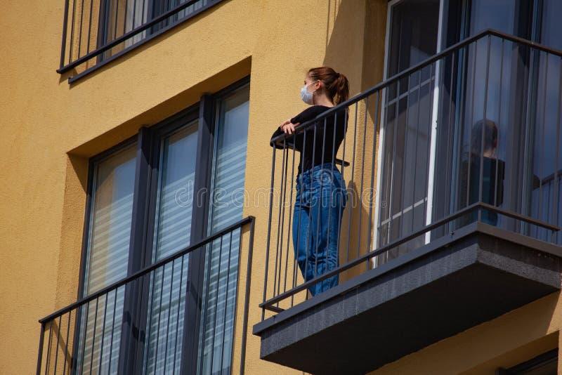 Femme masquée sur le balcon isolé de la maison photo libre de droits