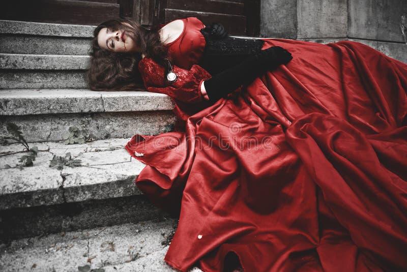 Femme menteuse et de saignée dans la robe victorienne images stock