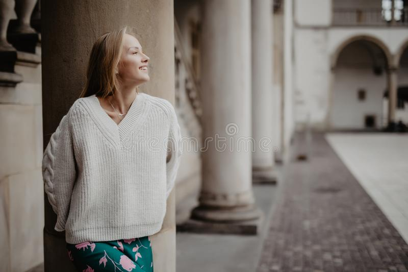 Femme merveilleuse de beauté posant et souriant près de la colonne et regardant l'appareil-photo dans la rue images stock