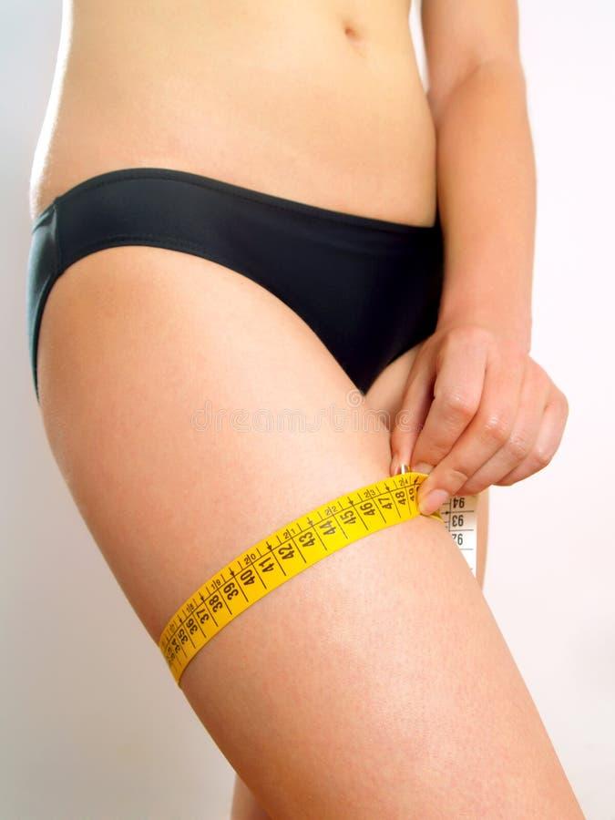 Femme mesurant sa cuisse image libre de droits