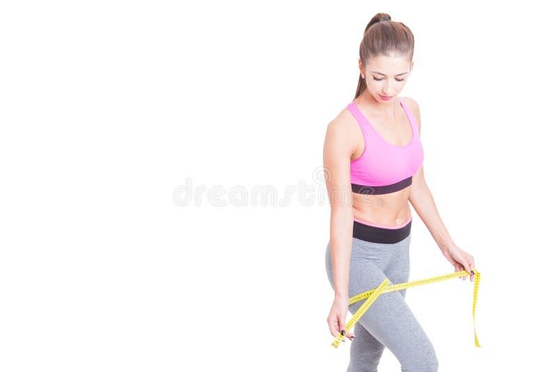 Femme mesurant sa jambe avec la ligne de bande photo stock