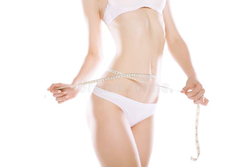 Femme mesurant sa taille par la bande métrique d'isolement photos stock