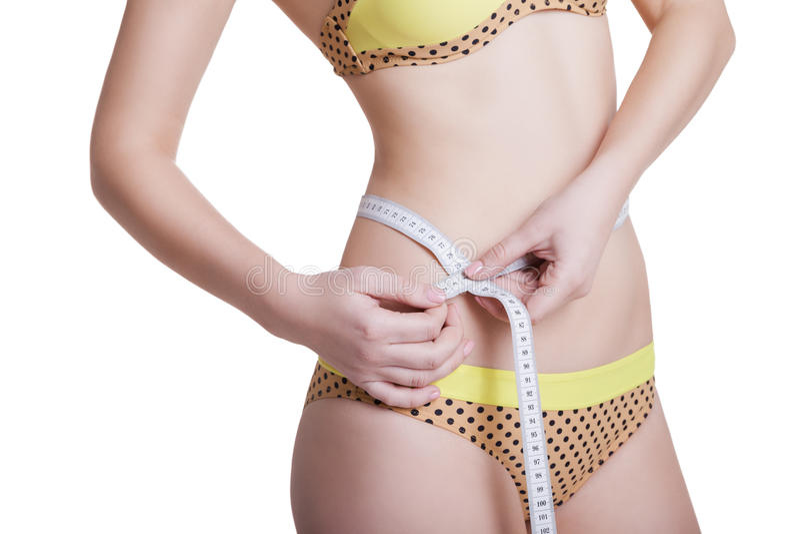 Femme mesurant son corps mince d'isolement photos stock