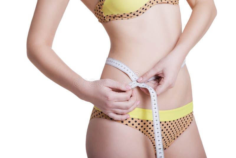 Femme mesurant son corps mince d'isolement image libre de droits