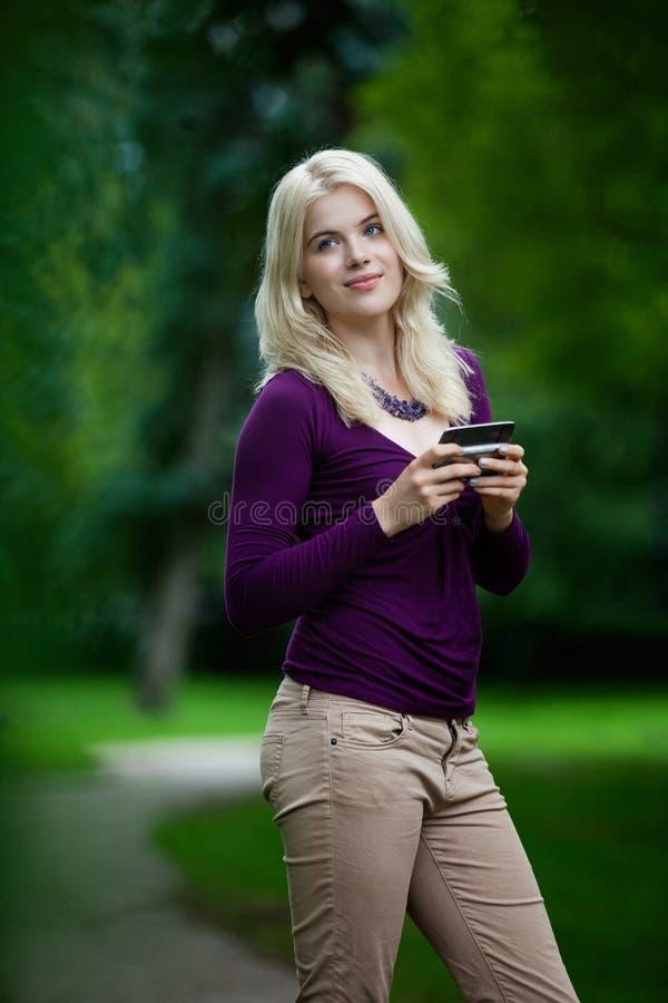 Femme mettant à jour le statut au téléphone portable images libres de droits
