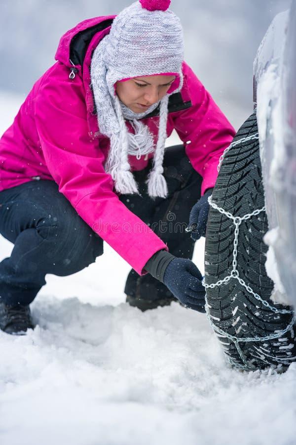 Femme mettant des chaînes d'hiver sur la voiture photographie stock