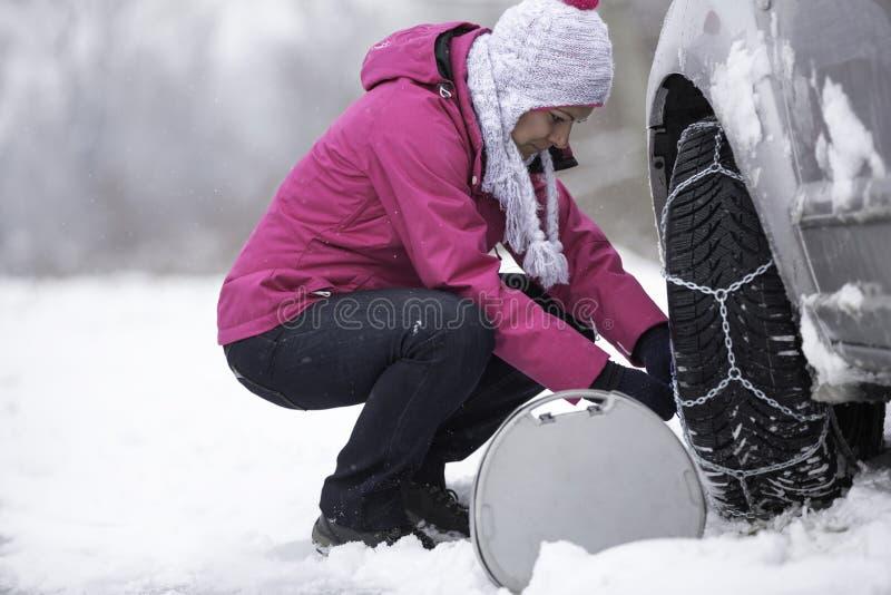 Femme mettant des chaînes de neige image stock