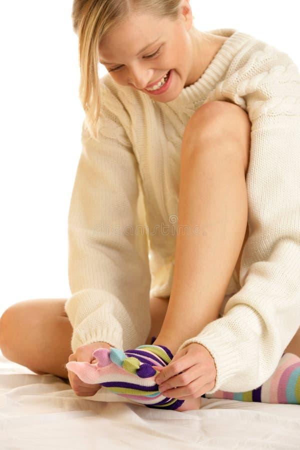 Femme mettant des chaussettes en fonction photographie stock