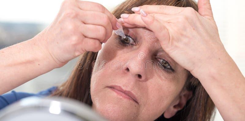 Femme mettant des gouttes pour les yeux dans son oeil images libres de droits