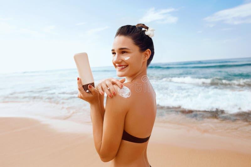 Femme mettant la lotion de sunblock sur l'?paule avant le bronzage pendant des vacances d'?t? sur le lieu de vill?giature de plag images stock
