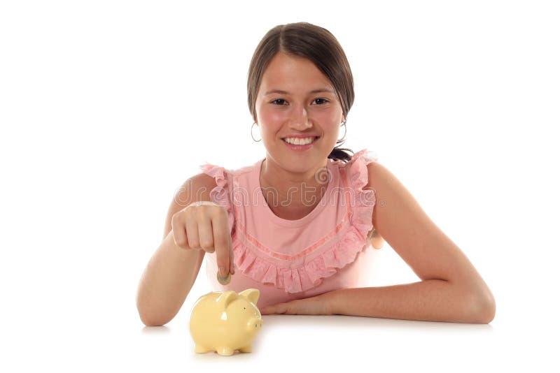 Femme mettant la pièce de monnaie à la tirelire images libres de droits