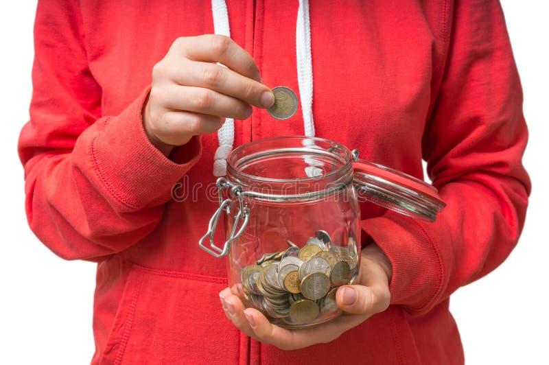 Femme mettant la pièce de monnaie dans le pot d'argent pour des dépenses inattendues photo stock