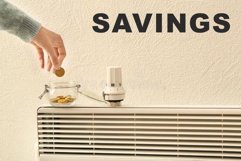 Femme mettant la pièce de monnaie dans le pot en verre près du thermostat sur le calorifer Concept économisant de chauffage photographie stock