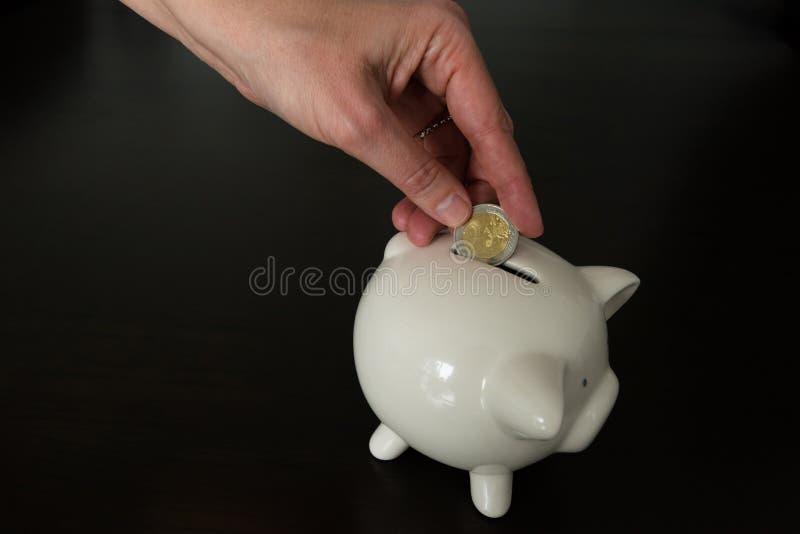 Femme mettant la pièce de monnaie de l'euro deux dans une tirelire images stock