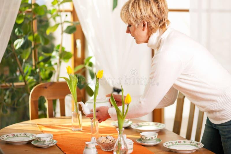 Femme mettant la table pour le thé du temps de café images stock