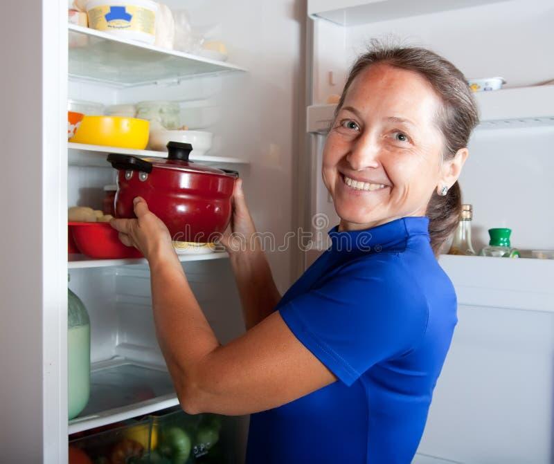 Femme mettant le carter dans le réfrigérateur photographie stock libre de droits