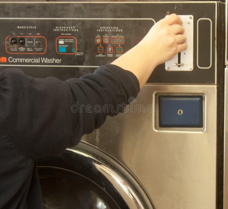 Femme mettant le quart dans la machine de Washin photographie stock libre de droits