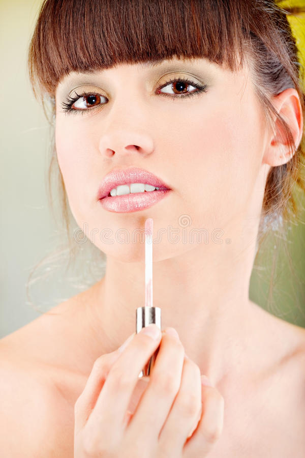 Femme mettant le rouge à lievres sur ses languettes image libre de droits