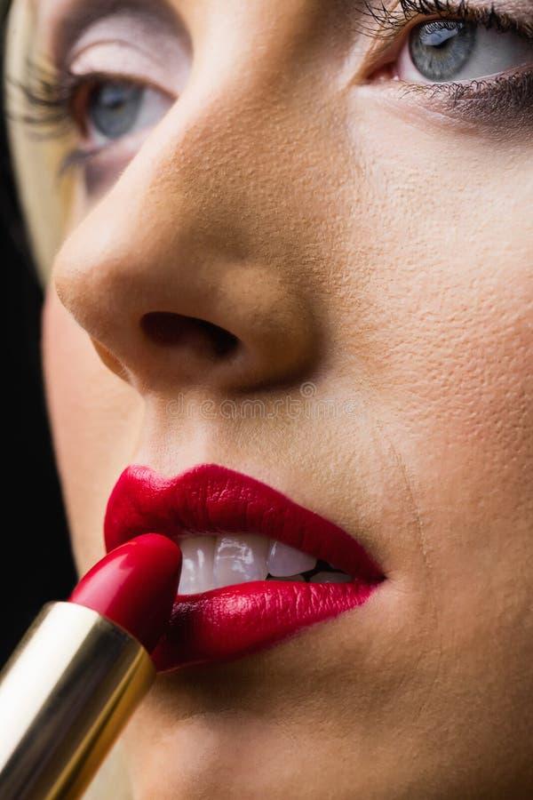 Femme mettant le rouge à lievres sur ses languettes image stock