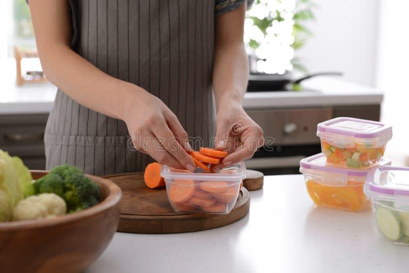 Femme mettant les tranches fraîches de carotte dans le récipient en plastique pour geler à la table dans la cuisine image libre de droits