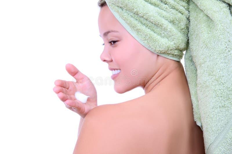 Femme mettant sur la lotion photographie stock libre de droits