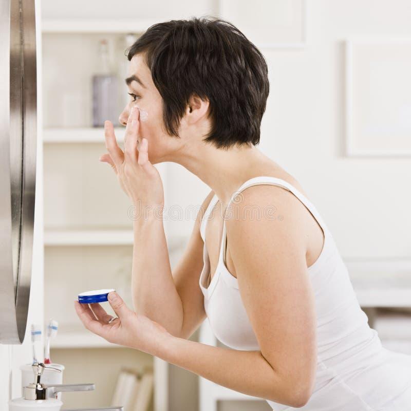 Femme mettant sur le renivellement image stock