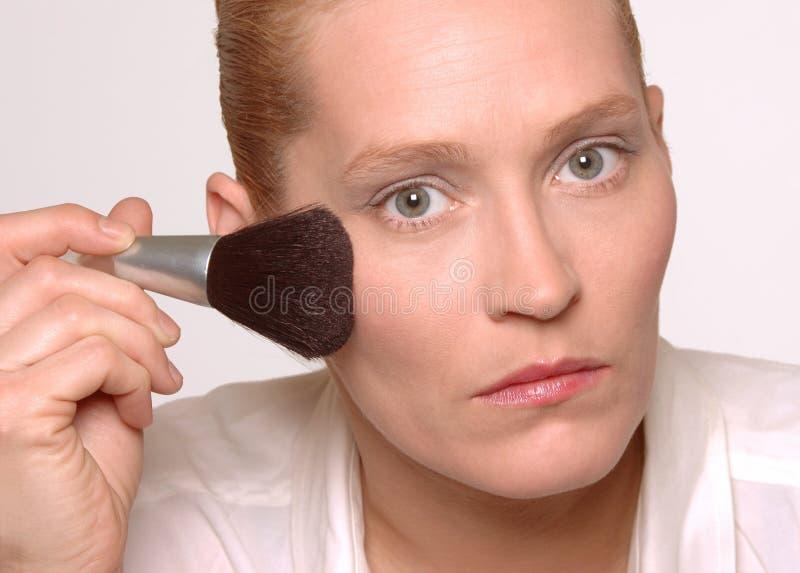 Femme mettant sur le renivellement photographie stock