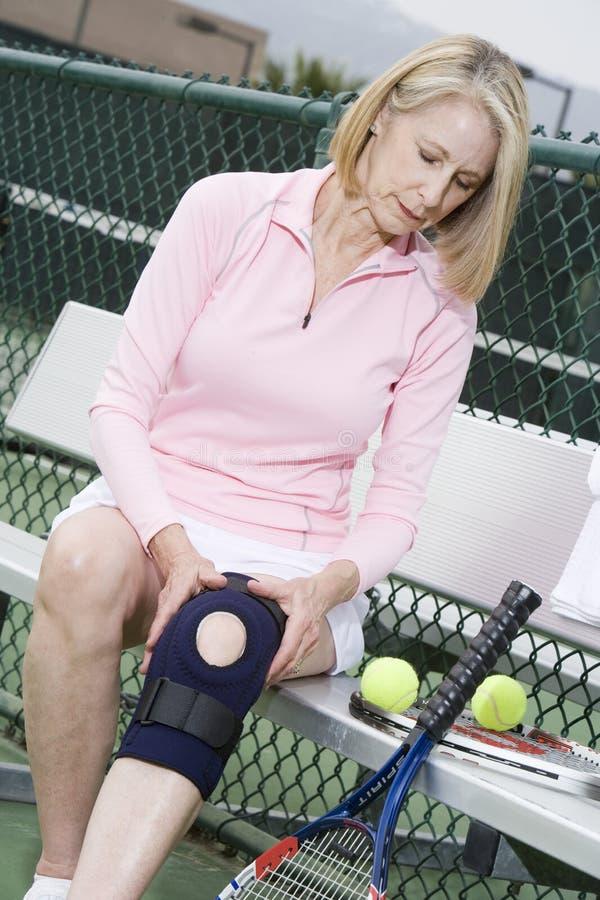Femme mettant sur une accolade de genou pour jouer au tennis photos libres de droits