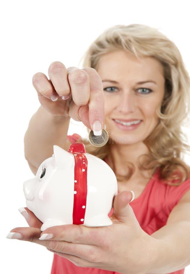 Femme mettant une euro pièce de monnaie dans la tirelire photographie stock libre de droits
