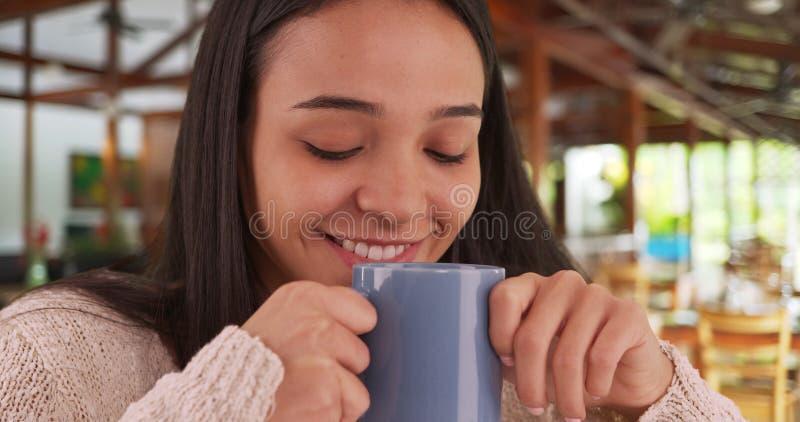 Femme mexicaine s'asseyant en café avec une tasse de café intéressante photos stock