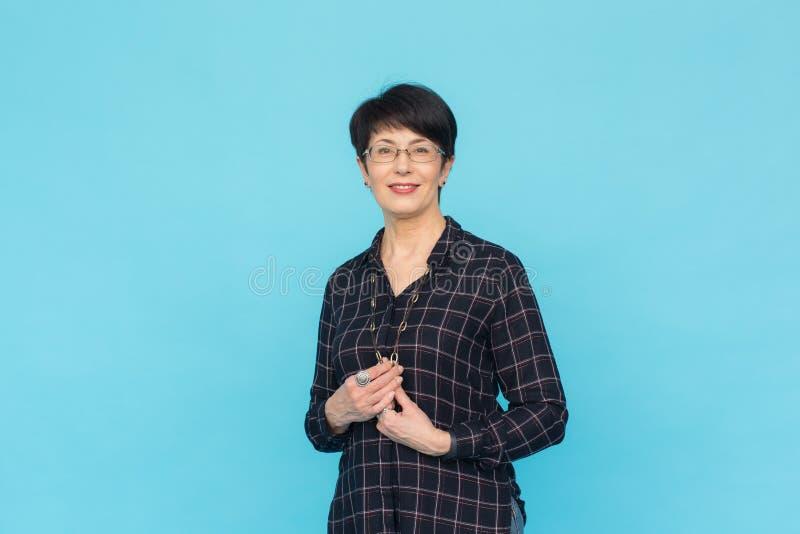 femme Mi-âgée avec la position de port en verre et de chemise de cheveux courts sur le fond bleu avec l'espace de copie photos stock