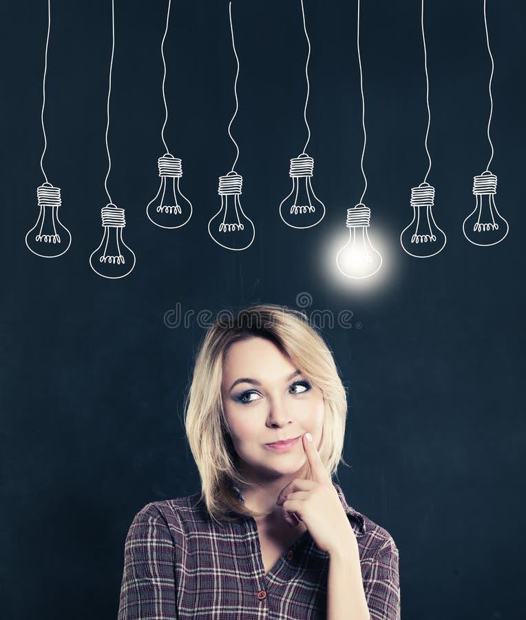 Femme mignonne avec l'ampoule sur le tableau noir photos stock