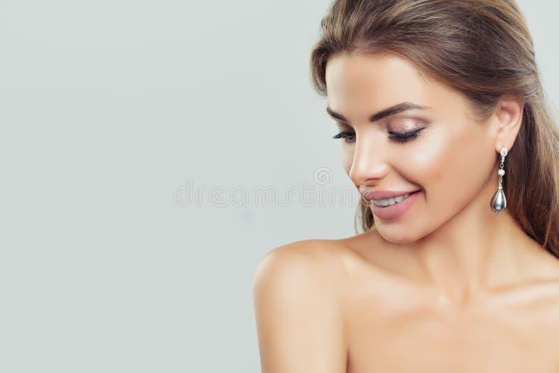 Femme mignonne avec le sourire noir de boucles d'oreille de perle image stock