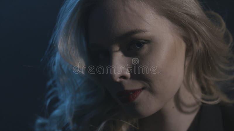 Femme mignonne avec les cheveux bouclés blonds regardant de côté sur le fond foncé action Belle jeune fille blonde avec long ondu photos stock